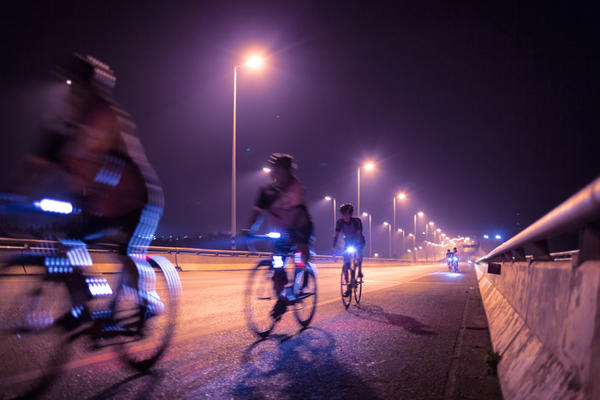 Photo of cyclists with bike lights on a road in the dark
