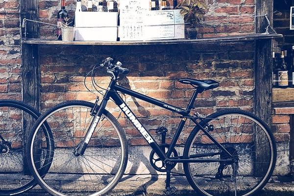 Image of a black bike with brick wall in background