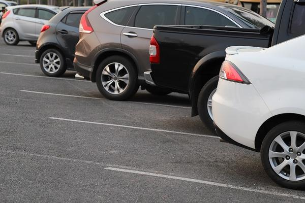 Closeup of rear, back side of white car with other cars parking in outdoor parking area in twilight evening.