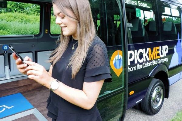 Image of person using a mobile phone to book the pickmeup bus service
